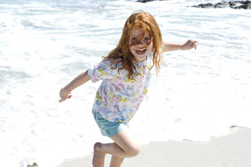 Little girl walking on the beach, outdoors
