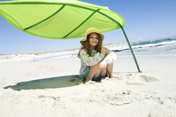 Little girl sitting on the beach under large green leaf, outdoors