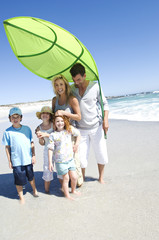 Parents and three children on the beach posing for the camera, outdoors