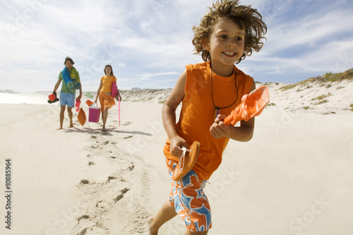 Parents and little boy walking on the beach, outdoors