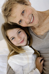 Senior woman and little girl smiling for the camera, indoors