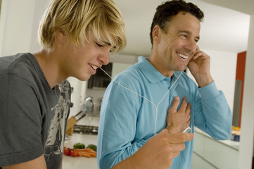 Father and son listening to music with MP3 player, indoors