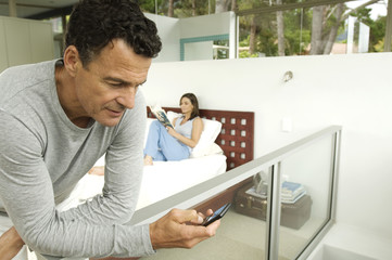 Couple in bedroom, man looking his cell, woman reading magazine, indoors