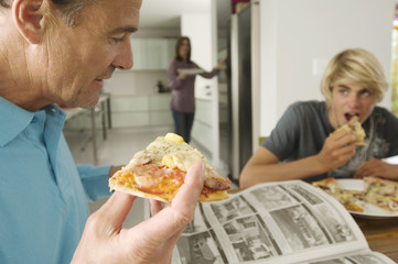 Father and teenager eating pizza, mother in background, indoors