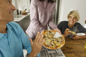 Parents and teen eating pizza, indoors