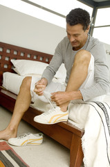 Man sitting on bed, tiying his baskets, indoors
