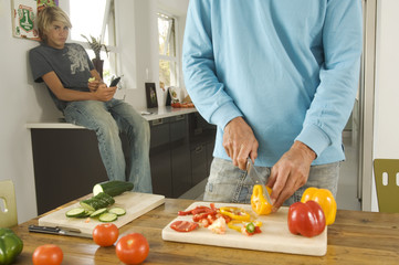 Man cooking, teen sitting in background, indoors