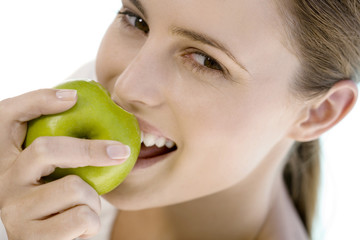 Portrait of a young woman eating an apple, indoors
