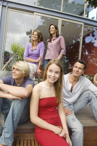 Parents and three teenagers in front of their house, indoors