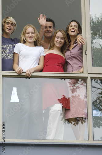 Parents and three teens behind window, looking at the camera, indoors