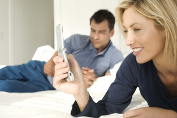 Young couple in bed, woman using mobile phone, man in background