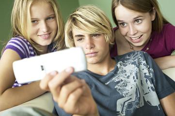 3 teenagers using camera phone