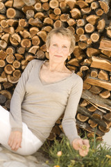 Senior woman sitting by woodpile