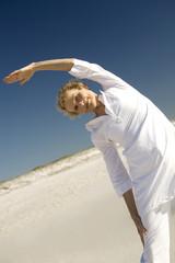 Senior woman stretching on beach