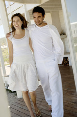 Smiling couple embracing, walking on wooden terrace