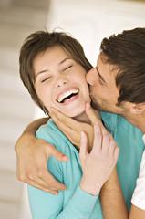 Portrait of man kissing smiling woman