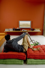 Man watching TV lying on cushions, vacuum cleaner in front of him