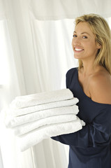 Young woman carrying stack of towels