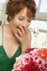Young woman looking at bunch of flowers, hand covering mouth