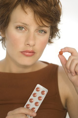 Portrait of a young woman holding pills