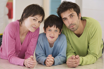 Parents and son looking at camera, lying on floor