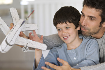 Father and son playing with model aeroplane