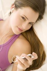 Young woman lying on bed, listening to music