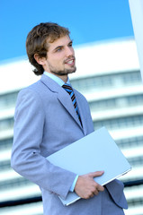 Young businessman holding file, side view