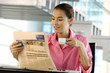 Businesswoman holding cup and reading newspaper in office