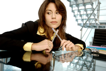 Young businesswoman holding pens