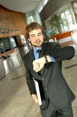 Young businessman looking at wristwatch