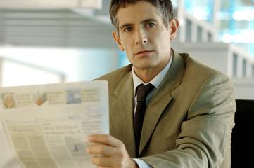 Mid adult businessman holding newspaper, portrait