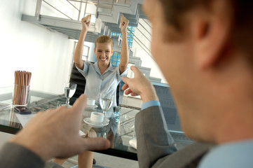Businessman pointing with young woman smiling in background