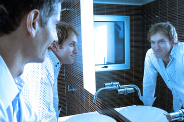 Men looking at mirror in washroom, smiling
