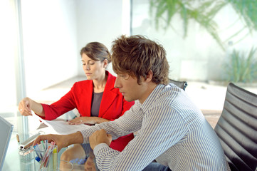 Businessman and businesswoman sitting in office