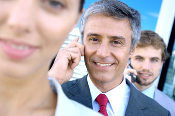 Business people using mobile phones, smiling