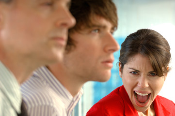 Businesswoman screaming with businessmen in foreground