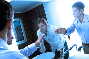 Young men looking at mirror in washroom