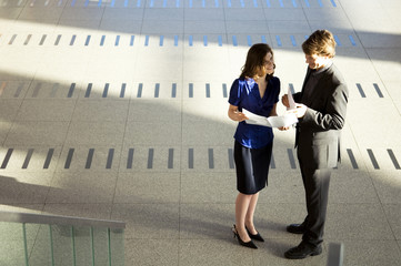 High angle view of a businesswoman showing a document to a businessman