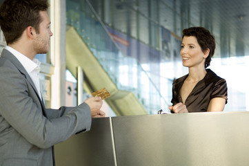 Businessman giving a credit card to a hotel receptionist