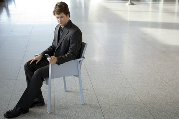 Businessman sitting in an armchair and text messaging with a mobile phone
