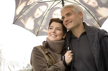 Close-up of a mid adult woman and a mature man under an umbrella