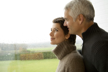Mid adult woman and a mature man standing by a window