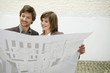 Mid adult man and a young woman looking at a blueprint