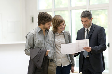 Real estate agent showing a blueprint to a couple