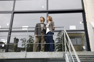 Low angle view of a mid adult man and a young woman standing at a balcony