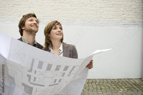 Mid adult man and a young woman holding a blueprint