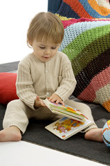 Close-up of a baby boy sitting and holding picture books