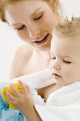 Close-up of a young woman wrapping her son in a towel and smiling