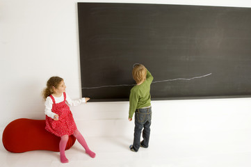 Rear view of a boy drawing on a blackboard with his sister sitting beside him